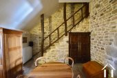 quiet room to the back of living room with stone staircase