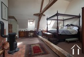 the master bedroom, with high ceilings and wood burner